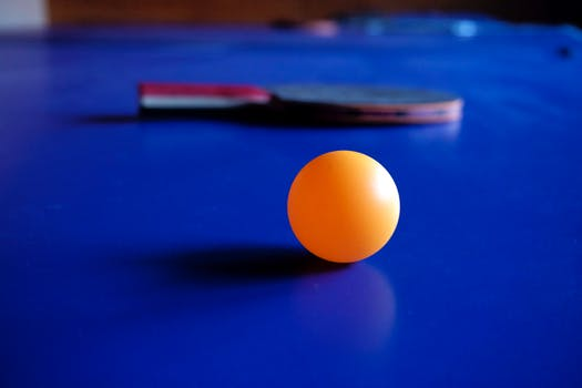 Bright orange ping pong ball on a bright blue table with a paddle.