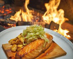Photo of a fish dinner from Forge and Vine next to the flames from the wood fired oven