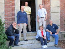 Members of the Concord Engineering team on stairs in front of a building