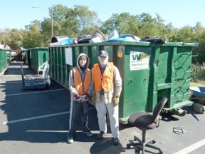 2 Men Standing Next to a Green Bin